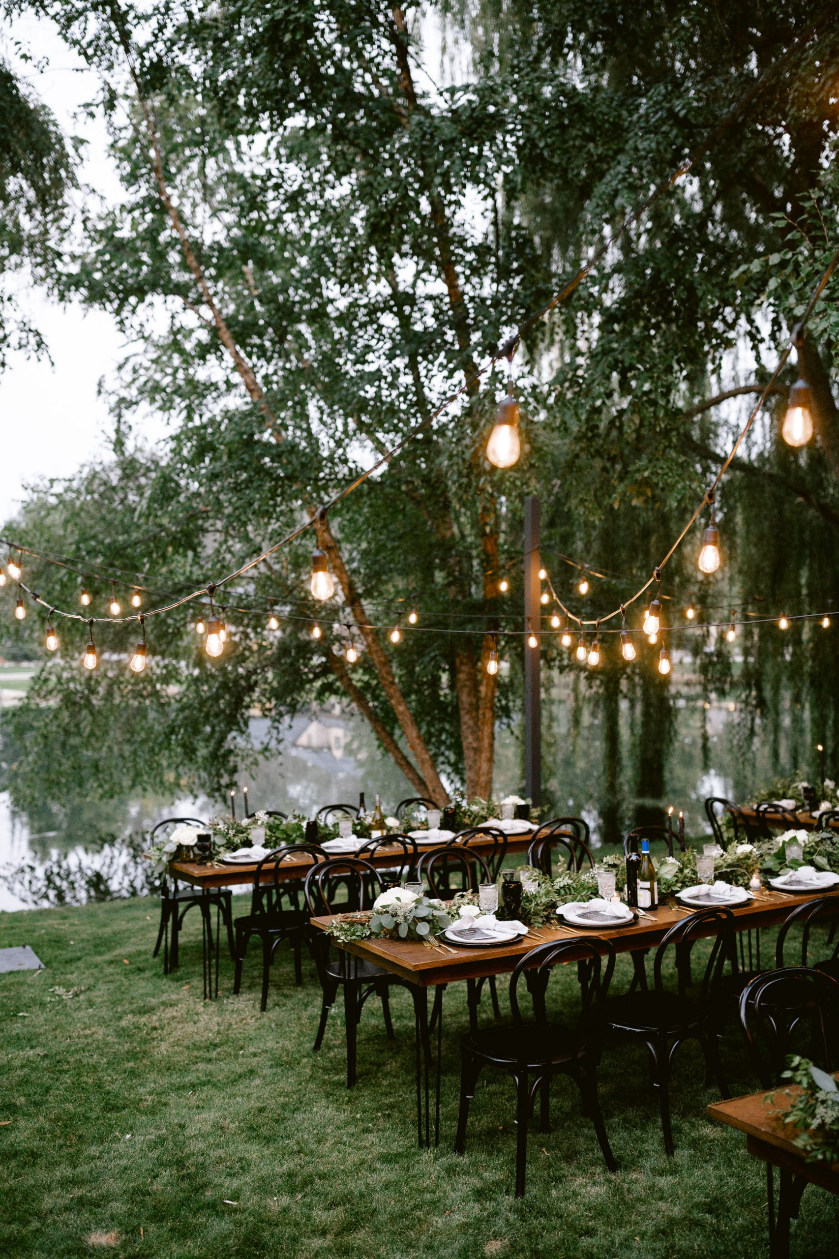 Everything about this set-up is magical!  Our modern white plates and gold flatware rentals look even better under strings of outdoor lights.