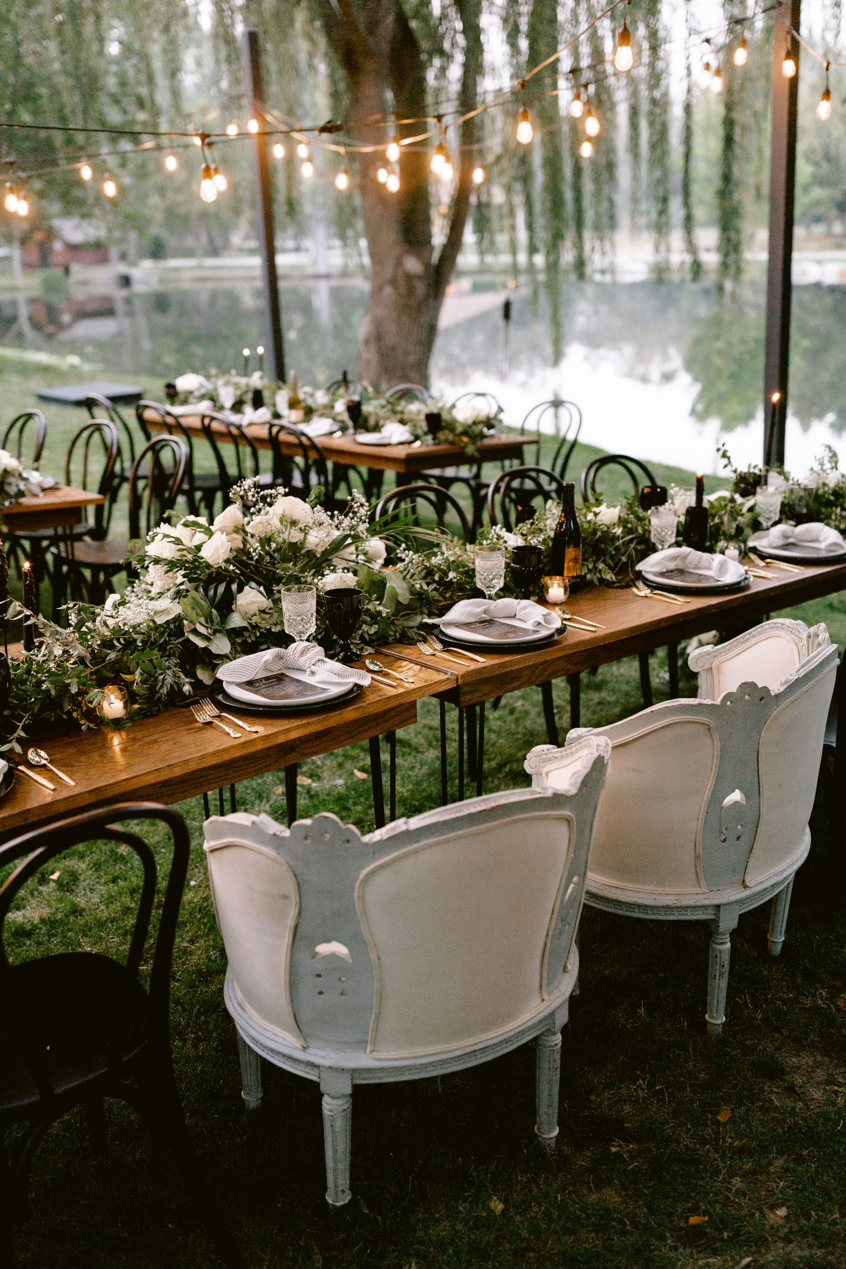 Elegant white chairs and florals perfectly contrast black chargers and black vintage goblets.