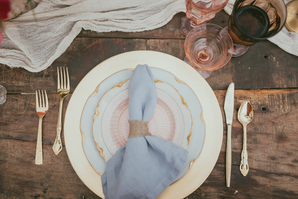 Our vintage gold china rentals paired with our storm blue napkins and vintage gold flatware.