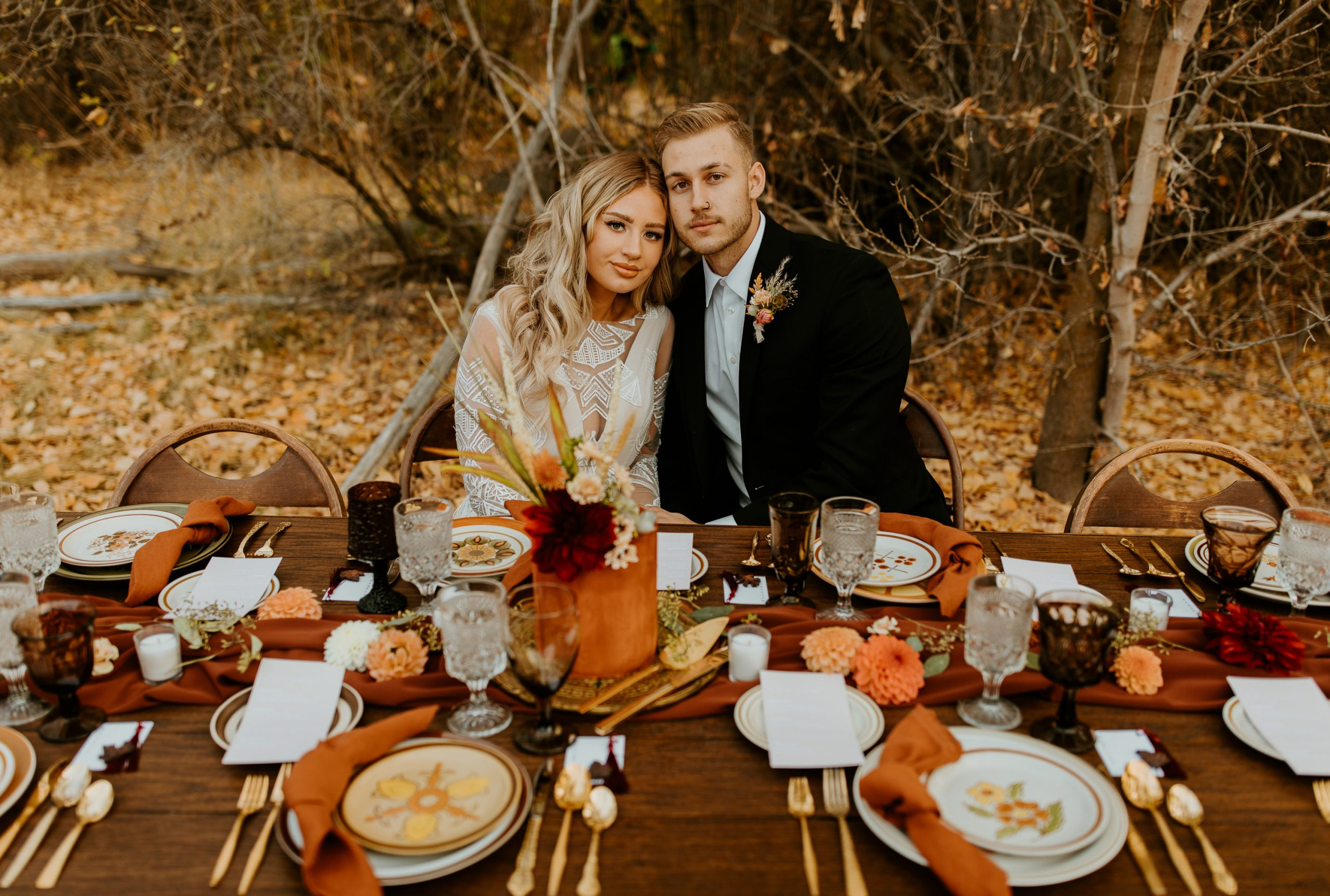 Burnt orange and deep red flowers are layered with our rust linen napkins and gold vintage flatware.